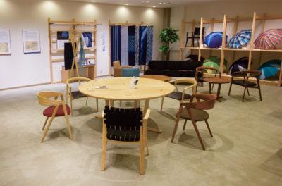 写真:中央に木工のテーブルと椅子があり、壁際にはパネル展示や商品棚のあるスペース