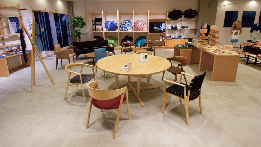 写真:丸い木のテーブルを様々な形の椅子が囲んでいる。