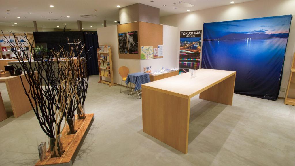写真:ハンプレットや地図、ポスターが並んだエリア。左手に黒と白の木の枝が並び、木製のハイテーブルが中央にある。