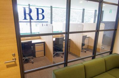写真:事務机が窓際に並んだレンタルブーススペースをドアの外から見たところ。ブースごとに板で区切られている。