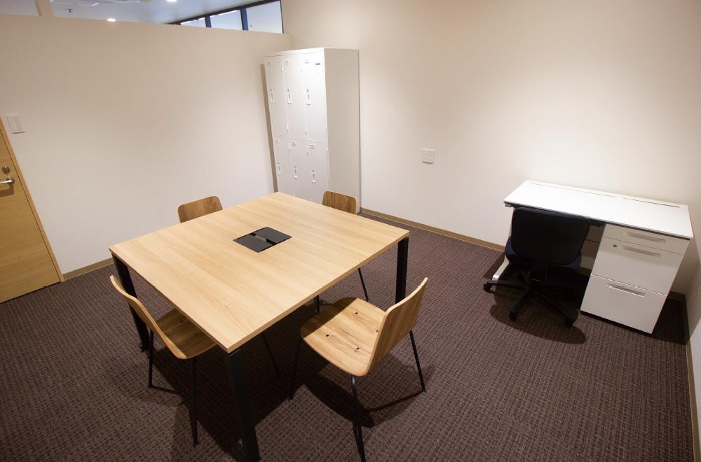 写真:中央にテーブルと4席の椅子、壁際に1席の事務机、ロッカーがある部屋。