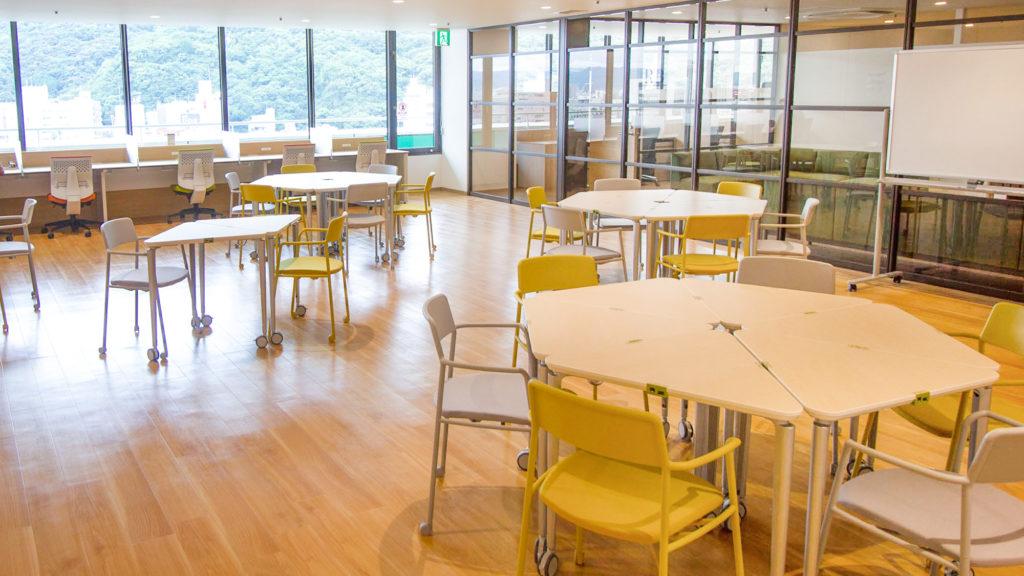 写真:六角形のテーブルと窓際にカウンター席の並んだスペース。