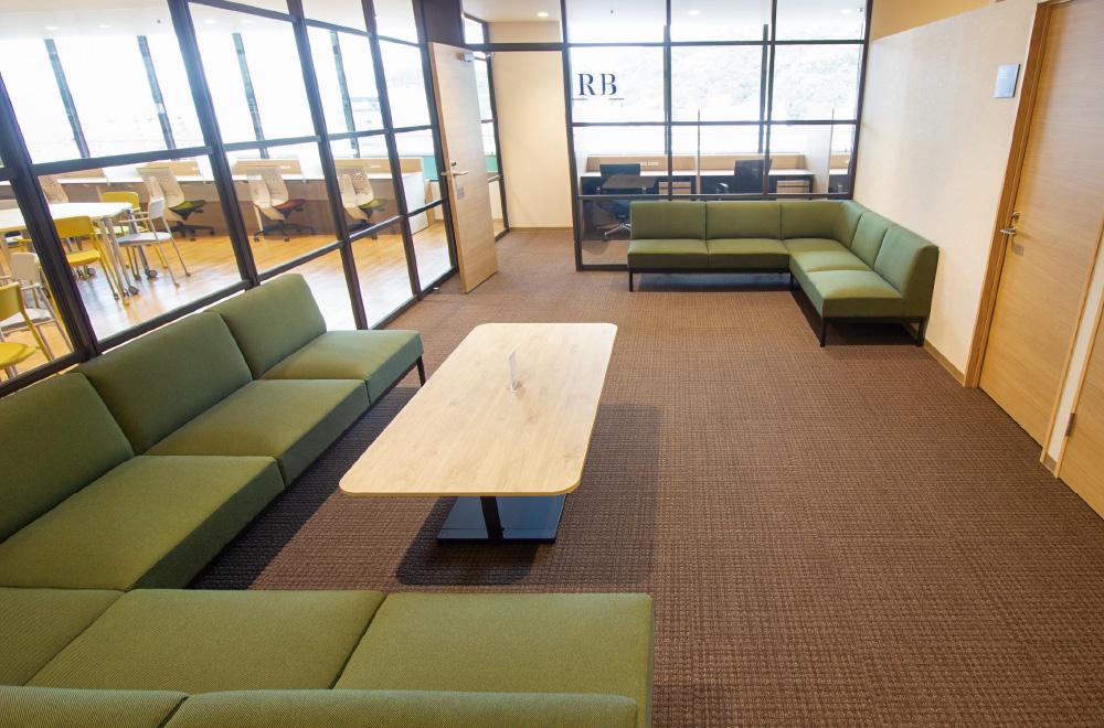 写真:L字型のグリーンのソファが2つあるスペース。一方にはテーブルもある。ガラス張りで明るい。