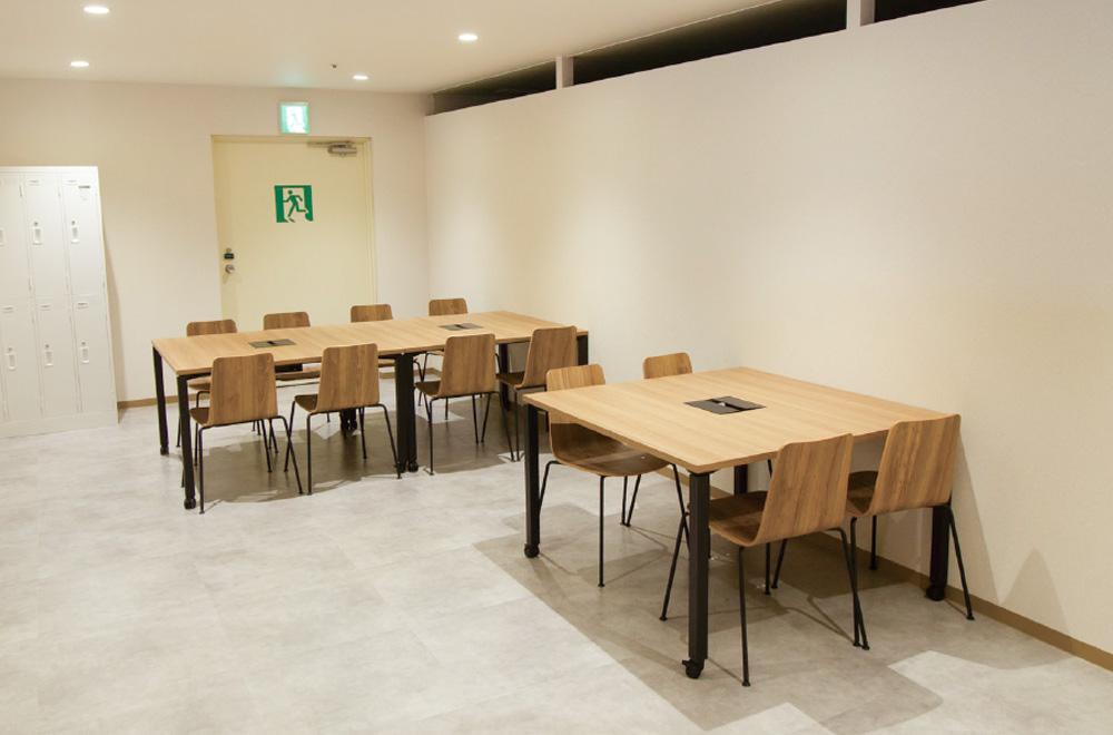 写真:大中2つのテーブルがあるスペース。大きなテーブルには8つ、中くらいのテーブルには4つの椅子がある。